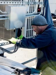 technician-performing-hvac-maintenance-on-roof
