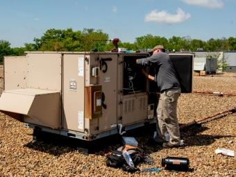 technician-performing-maintenance-on-hvac-on-roof