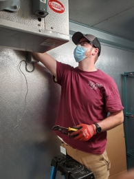 masked-technician-serving-refrigerator